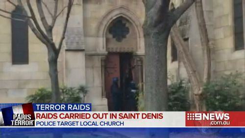 Police officers smash their way into the Denis de l'Estree church, near the site of the siege. (9NEWS)