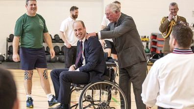 The Duke of Cambridge has his shoulders rubbed by the Prince of Wales after he attempted and failed to throw a basket ball into the hoop while playing wheelchair basket ball during a visit to the Defence Medical Rehabilitation Centre Stanford Hall