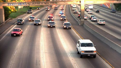 A white Ford Bronco, driven by Al Cowlings carrying O.J. Simpson, is trailed by Los Angeles police cars as it travels on a freeway in Los Angeles. Simpson's ex-wife, Nicole Brown Simpson, and her friend Ronald Goldman had been found dead in Los Angeles, four days earlier. Simpson is later arrested after a widely televised freeway chase in his white Ford Bronco.