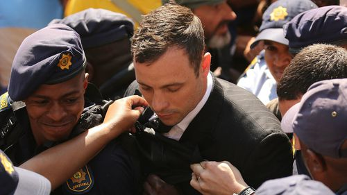 Oscar Pistorius is escorted by police. (AAP)