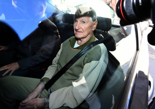 Vincent O'Dempsey sits in the back of a police car. Queensland Police said Mr O'Dempsey was 'surprised' when they turned up for him today.