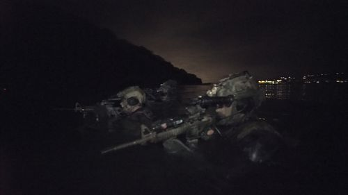 The divers surface - weapons at the ready - as they move up the beach. (9NEWS)