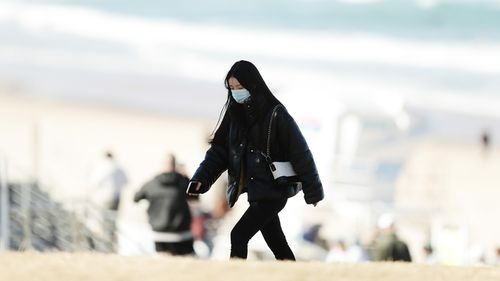 A woman wears a face mask at Bondi Beach in Sydney.