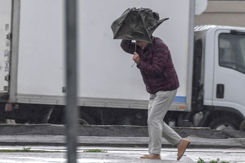 Commuters are battling against their umbrellas as wind combines with downpours of rain. Picture:AAP