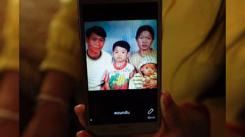 Soccer coach Ekkapol Ake Chantawong, seen here as a boy in the center of this photo with his late parents and younger brother. Picture: CNN