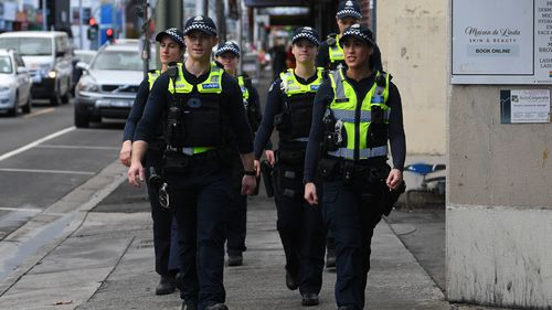 Victoria Police officers patrol near Victoria Street in Richmond.