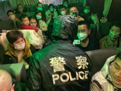 Police stop a bus to do registration and temperature checks in Zhejiang Province, China