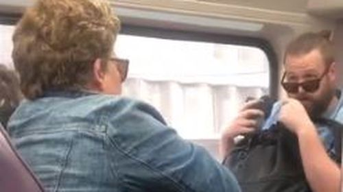 Woman coughs on commuter sparking bitter argument amid coronavirus fears.