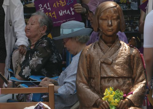 Two former South Korean victims sit next the statue symbolising a comfort woman in Seoul on August 15, National Liberation Day.