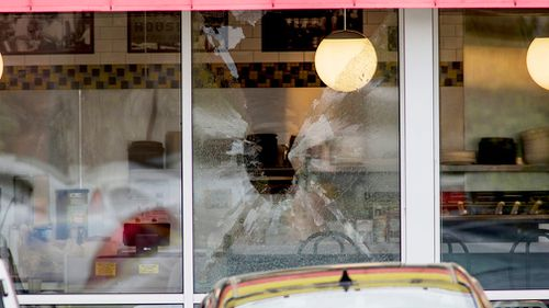 A shattered window at the scene of the shooting. (AP)