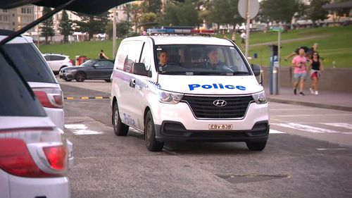 A NSW Police van drives through a Bondi Beach carpark. Around 70,000 police officers are patrolling the social distancing orders.