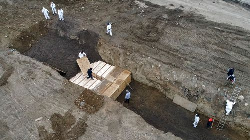 Workers wearing personal protective equipment bury bodies in a trench on Hart Island in New York.