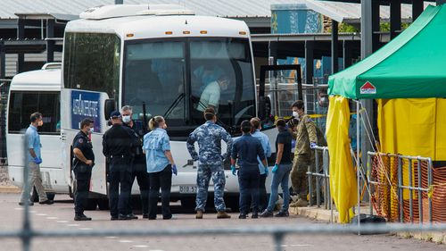 Multiple government agencies gather beside buses to take Australian evacuees from the coronavirus-struck cruise ship Diamond Princess after they arrived on a Qantas flight from Japan at Darwin International Airport in Darwin, Thursday, February 20, 2020.