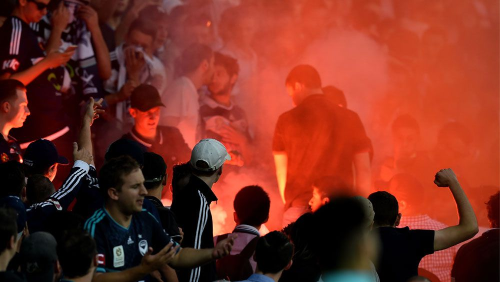 Flare-wielding fans strike police, players with missiles