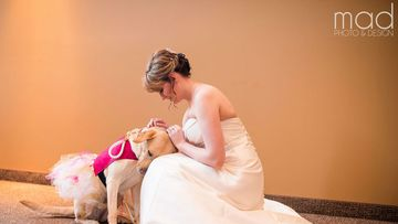 Bella, the service dog in a tutu, comforts her owner Valerie Parrot on her big day. (Maddie Peschong)