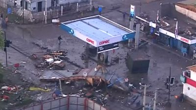 Debris surrounds a fuel station.