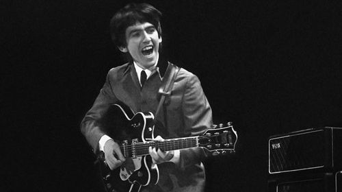George Harrison performing with the Beatles in 1964. (AAP)