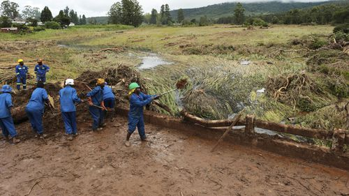 Women clear mud and debris from a bridge in Chimanimani about 600 kilometres south east of Harare, Zimbabwe, Tuesday, March, 19, 2019.