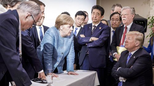 German Chancellor Angela Merkel, center, speaks with U.S. President Donald Trump, seated at right, during the G7 Leaders Summit in La Malbaie, Quebec, Canada (Photo: June 2018)