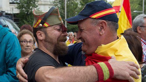 A man in a legionnaires uniform hugs a man draped in a Spanish flag. (AP)
