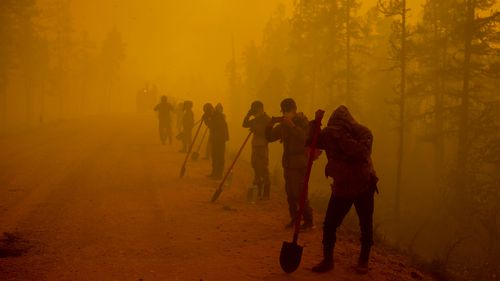 Volunteers pause while working at the scene of forest fire near Kyuyorelyakh village at Gorny Ulus area west of Yakutsk.