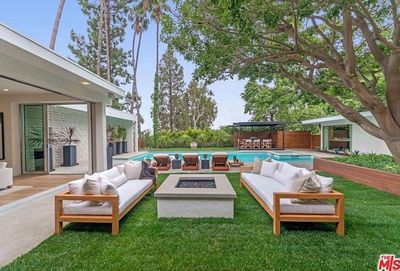 The impressive outdoor space has a pool, fire pit and a dining pavillion.