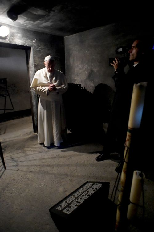 Pope Francis prays in the underground prison cell of a Catholic saint, Maximilian Kolbe, at the former Nazi German death camp of Auschwitz in Oswiecim, Poland. (AAP)