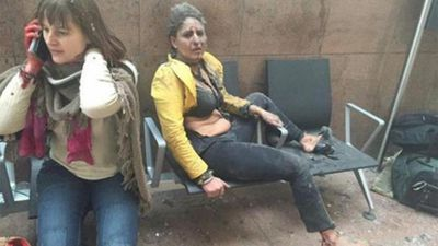 Women bloodied and covered in dust sit at the airport in shock moments after the twin blasts.