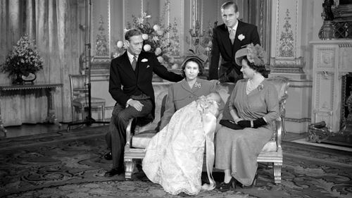 A young Prince Charles sleeps in his mother's arms following his christening at Buckingham Palace in 1948. (AAP)