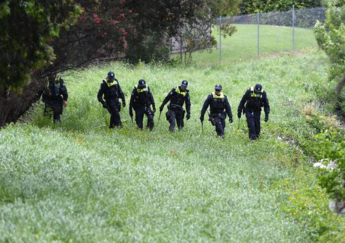 Police conduct a line search at Dandenong Creek in Bayswater in Melbourne. The police were looking for clues after Paul Virgona was found dead in a van on the Eastlink Freeway.