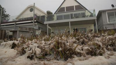 Sea foam coats the grass outside a beachfront home in Collaroy.