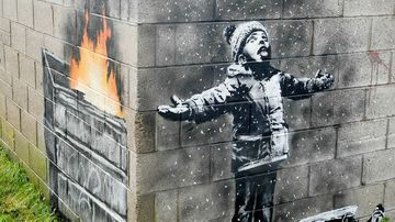 An artwork by Banksy on the side of a garage depicts a child dressed for snow playing in the falling ash and smoke from a skip fire, in Port Talbot, Wales.