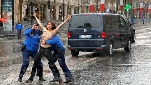 The protester, with the words 'fake peacemaker' written on her chest, is tackled by police.