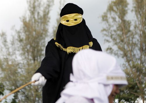 A sharia law enforcer, know as algojo, delivers a public punishment in Aceh, Indonesia. The Sharia Court in Aceh appoints those into the job of Algojo. With masked robes from head to foot to protect their identities, the algojo carry out punishments, including public whipping with a bamboo cane, as deemed by the court.