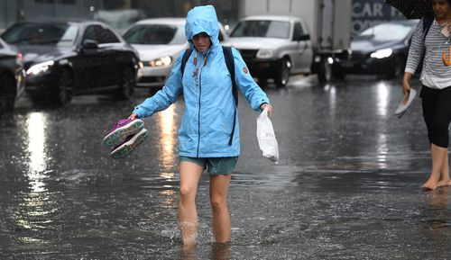 Pedestrians walk through flood waters at the corner of Clarendon and Cecil Street in South Melbourne,