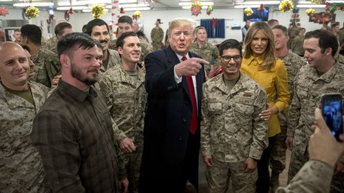 President Donald Trump and first lady Melania Trump pose for a photograph as they visit members of the military at a dining hall at Al Asad Air Base, Iraq