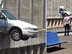 Car dangles over tracks after driver crashes through wall