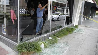Alan Mathison works at cleaning up a broken storefront window following an earthquake Sunday, Aug. 24, 2014, in Napa, Calif. (AAP)