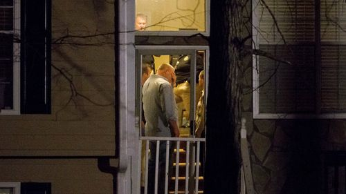 Detectives inside a home near Atlanta, Georgia where the bodies of five people were found. (AAP)
