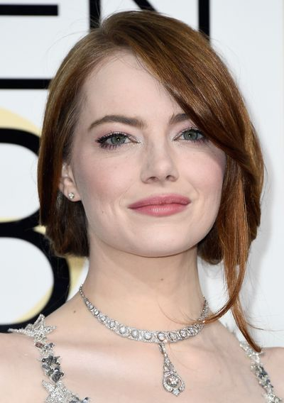 <p>Emma Stone wore her hair swept up with a loose lock or two for a casually lovely effect. Eyes were sparkling with silver shadow. Lips were coated with a touch of soft pink gloss.</p> Image: Getty.