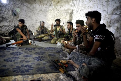 A motley crew of fighters with the Free Syrian army eat in a cave where they live, in the outskirts of the northern town of Jisr al-Shughur, Syria, west of the city of Idlib.