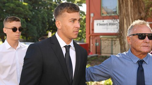 St. George Illawarra Dragons junior player Callan Sinclair (centre) arrives at Wollongong Local Court in Wollongong.