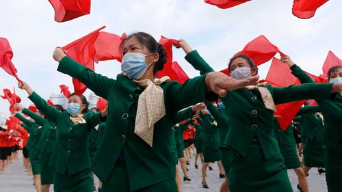 Women parade with flags during a rally to welcome the 8th Congress of the Workers' Party of Korea in the Party at Kim Il Sung Square in Pyongyang, North Korea.