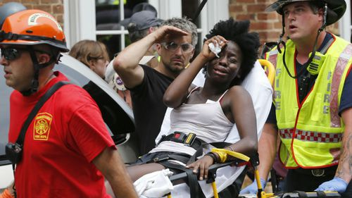 Rescue personnel help an injured woman after a car ran into a large group of protesters after an white nationalist rally in Charlottesville on Saturday. (AP)