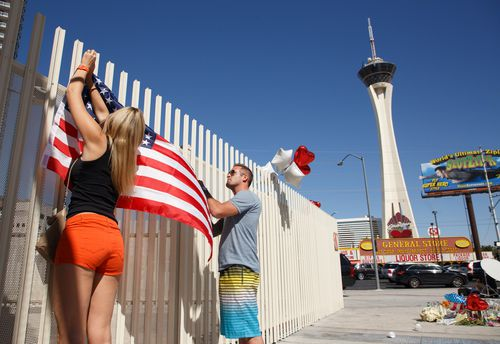 Mourners erect a US flag near the Stratosphere Tower as part of a makeshift memorial to the victims of the mass shooting in Las Vegas. (AAP)