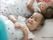Separated twins intertwine legs and 'need to be touching'