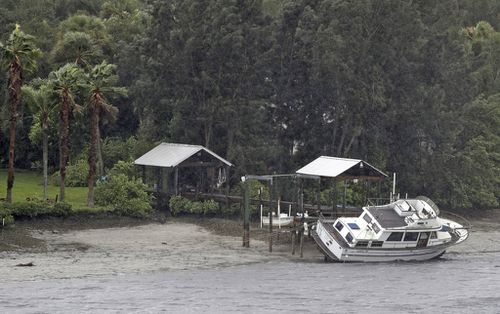A boat rests on its side in what is normally six feet of water in Old Tampa Bay. (AP)