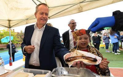 Federal Labor leader Bill Shorten buys a sausage after voting at Moonee Ponds West Primary School in Melbourne.