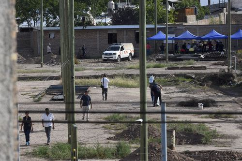 Police work in the lot next to the home of Gilad Pereg where the bodies of his mother and aunt were found in Mendoza, Argentina, on Saturday.