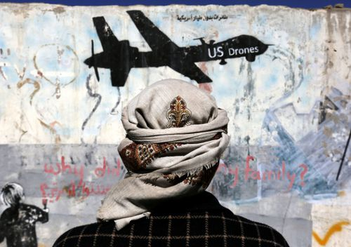 A Yemeni stands in front of graffiti protesting US drone operations in war-affected Yemen.